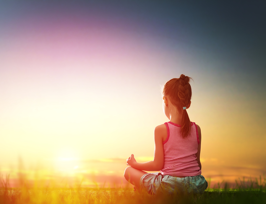 Child girl in the Park. Yoga at sunset in the park. Girl is prac